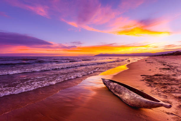Lake Malawi sunset in Kande beach Africa, canoe boat on beach peaceful beach holiday beautiful sunset colors blue purple orange yellow in sky and clouds